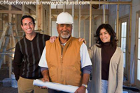 Picture of a man and woman couple with a general contractor in a white hard hat holding blueprints.